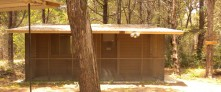 CABIN 9 –1 Queen Size Bed, Futon that makes into Bed, Indoor Shower & Bath with Closet, Large Refrigerator, Gas Stove, Microwave, Coffee Pot, Ceiling Fan, Local TV, A/C, Screened-In Porch.  No Smoking indoors Please.